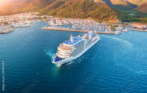 Cruise ship at harbor. Aerial view of beautiful large white ship at sunset. Colorful landscape with boats in marina bay, sea, green forest. Top view from drone of yacht. Luxury cruise. Floating liner © den-belitsky