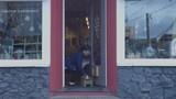 Handheld shot of female owner hanging open sign on door at plant shop - 190467278