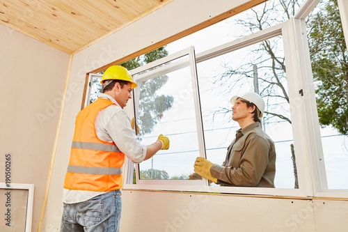 Monterzy montują okna w pracy zespołowej