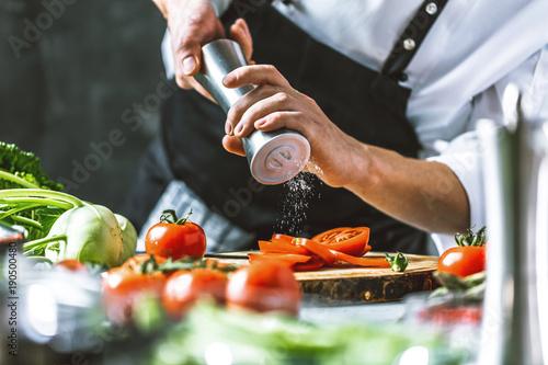 Poster Chefkoch in der Küche mit Frischem Gemüse(Tomaten)