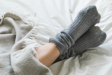 Feet up in cozy woolly pink socks with cup of tea and candles © lukesw