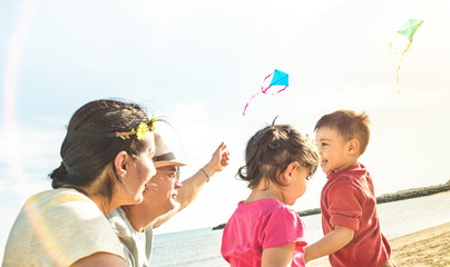 Happy family with parents and children playing together with kite at beach vacation - Summer joy concept with mixed race people having pure genuine fun together - Warm sunshine backlight filter