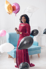 Gentle black girl with beautiful makeup and curly hair in a purple dress holding ballons, celebrating birthday © schepniy