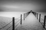 Fototapeta Most - Long exposure image of old abandoned fisherman jetty in black and white © asnidamarwani