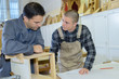 two designers working together in workshop with precision tools - 190520663