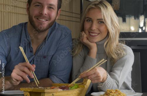 Foto Murales Pareja comiendo una barca de sushi en el restaurante.