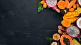 Tropical fruits, papaya, Dragon Fruit, rambutan, tamarind, cactus fruit, avocado, granadilla, carambola, kumquat, mango, mangosteen, passionfruit, coconut. On a wooden background. - 190527266