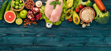 Healthy food. Chicken fillet, avocado, broccoli, fresh vegetables, nuts and fruits. On a wooden background. Top view. Copy space. - 190527414
