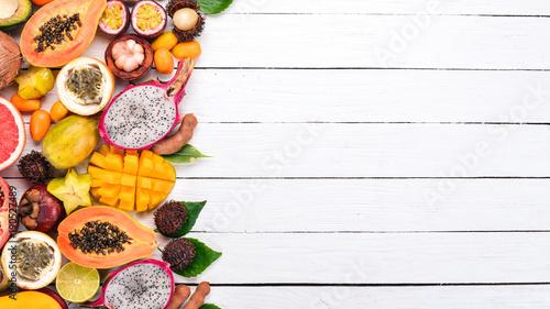 Owoce tropikalne, papaja, owoc smoka, rambutan, tamaryndowca, owoce kaktusa, awokado, granadilla, carambola, kumkwat, mango, mangostan, męczennica jadalna, kokos. Na drewnianym tle.