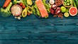 Healthy food. Fish salmon, avocado, broccoli, fresh vegetables, nuts and fruits. On a wooden background. Top view. Copy space.