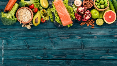 Wall mural Healthy food. Fish salmon, avocado, broccoli, fresh vegetables, nuts and fruits. On a wooden background. Top view. Copy space.