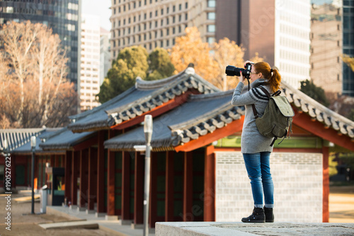 Fotobehang Seoel A woman traveler photographs an ancient palace in South Korea