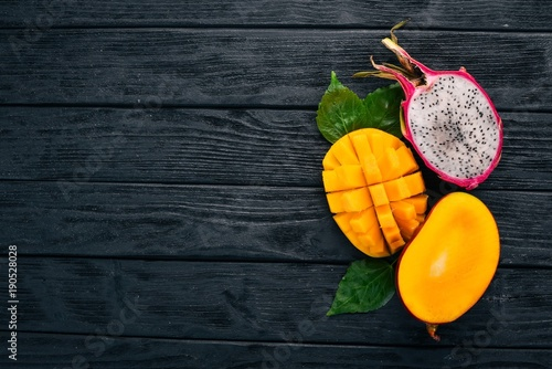 Mango and Dragon Fruit. Fresh Tropical Fruits. On a wooden background. Top view. Copy space.