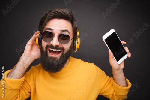 Fotobehang Muziek Excited man with smartphone and headphones