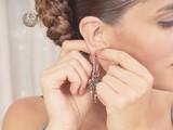 Beautiful woman is wearing the earrings in regional customes - 190533650