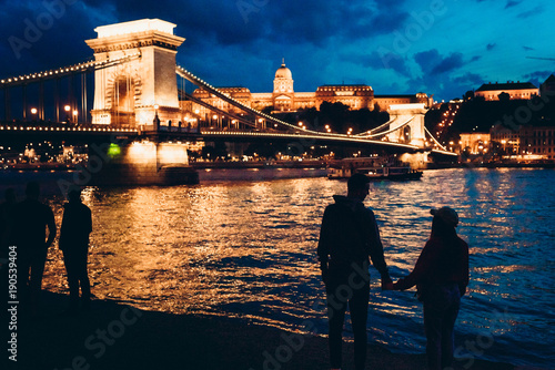In de dag Boedapest Two silhouettes of the loving couple holding hands on the riverbank of Danube and enjoying the beautiful landscape view of the shining Chain Bridge in Budapest, Hungary at night.