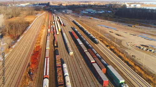 Looking down on industrial railroad train yard, many trains, tracks. Dynamic aerial view.