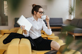 Young amazing business lady writing notes drinking coffee.