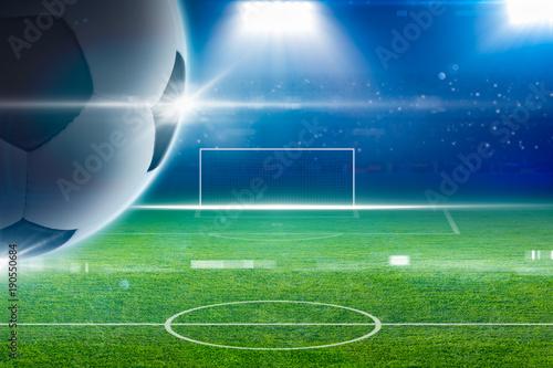 Big soccer ball above green stadium with bright spotlights