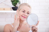 Forty years old woman looking at wrinkles in mirror. Plastic surgery and collagen injections. Makeup. Macro face. Selective focus - 190551047