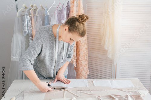Young seamstress makes clothes cutting fabric