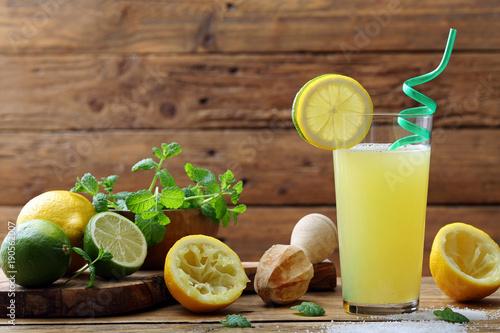 Fotobehang Sap succo di limone e lime in bicchiere su sfondo tavolo legno