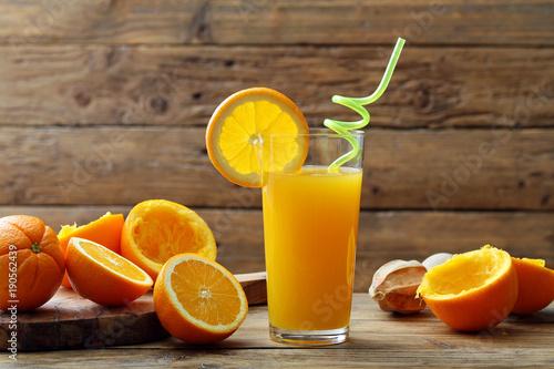 Fototapeta succo di arancia gialla in bicchiere su sfondo tavolo di legno