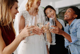 Woman in bridal gown toasting champagne glasses with friends - 190567681