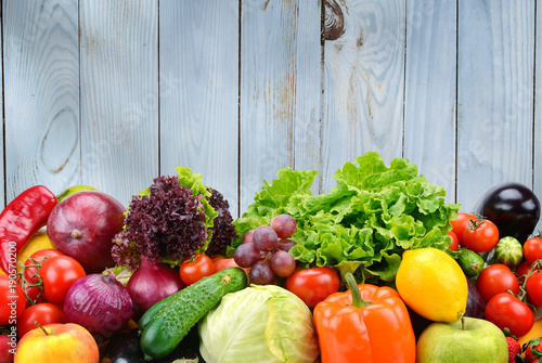 Useful vegetables and fruits on light blue wooden wall background