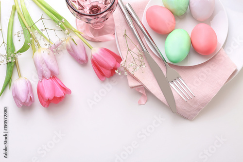 Beautiful festive Easter table setting with flowers and painted eggs on white background - 190572890