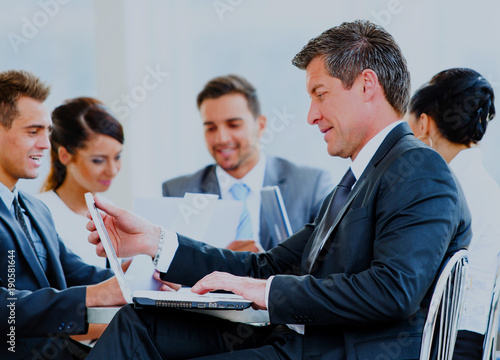 Happy businessman using laptop in business building, smiling.