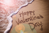Happy Valentine's Day message handwritten on smooth sand beach with incoming wave and romantic lens flare