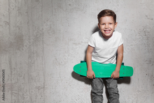 Fotobehang Skateboard Attractive little boy with green skateboard in his hands. Smiling guy in white T-shirt standing near grunge concrete wall. Concept of activity and happy childhood.