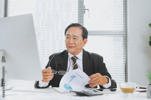 Senior financial asian businessman sitting at his workstation in front of computer.