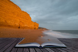 Creative book image of Beautiful vibrant sunset landscape image of Burton Bradstock golden cliffs in Dorest England - 190606094