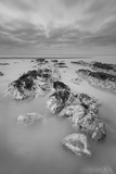 Stunning black and white long exposure landscape image of low tide beach with rocks at sunrise - 190606432