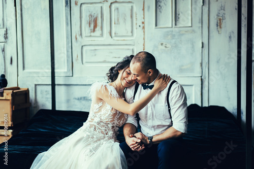 Happy couple in love having fun indoors and smiling. Bride and groom