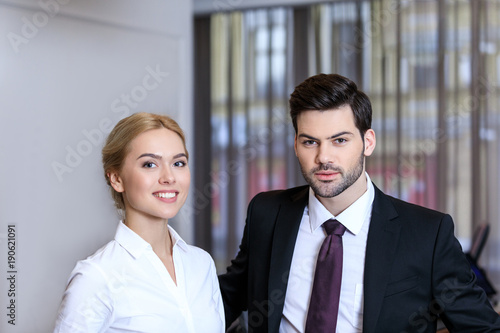 businessman and businesswoman standing at reception desk in hotel