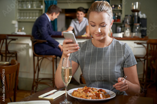 Female Food Blogger Posting Online Review Of Restaurant Meal Using Mobile Phone