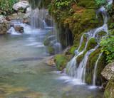 Veduta di un corso d'acqua che scorre veloce sulle rocce e sul muschio - 190636683
