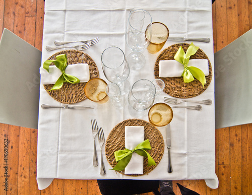 Fotobehang Pizzeria table set with plates and cutlery and glasses and a beautiful green bow