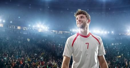 Happy soccer player on a football stadium