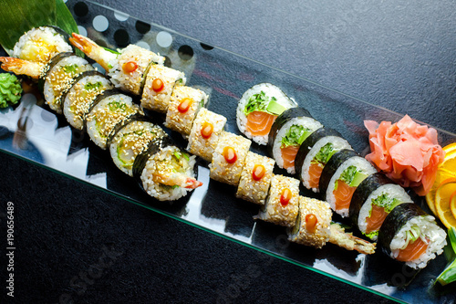 Tuinposter Sushi bar Sushi rolls set served on glass plate on dark background