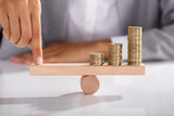 Businessperson Balancing Coins On Wooden Seesaw - 190662072