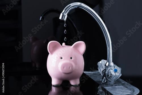 Spada kapiąca kropla wody z kranu w środku piggybank