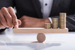 Businessperson Balancing Stacked Coins On Wooden Seesaw - 190683827