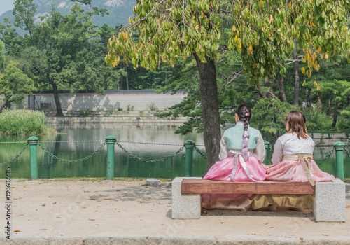Keuken foto achterwand Seoel Two young women in traditional Korean clothing sitting on a bench, enjoying a beautiful water view, at Gyeongbokgung Palace, Seoul, South Korea