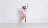 happy child girl jumping around empty wall - 190689417