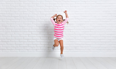 happy child girl jumping around empty wall