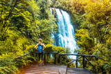 Woman hiker enjoys waterfall view from viewpoint surrounded by lush forest and vegetation. Chile - 190698629
